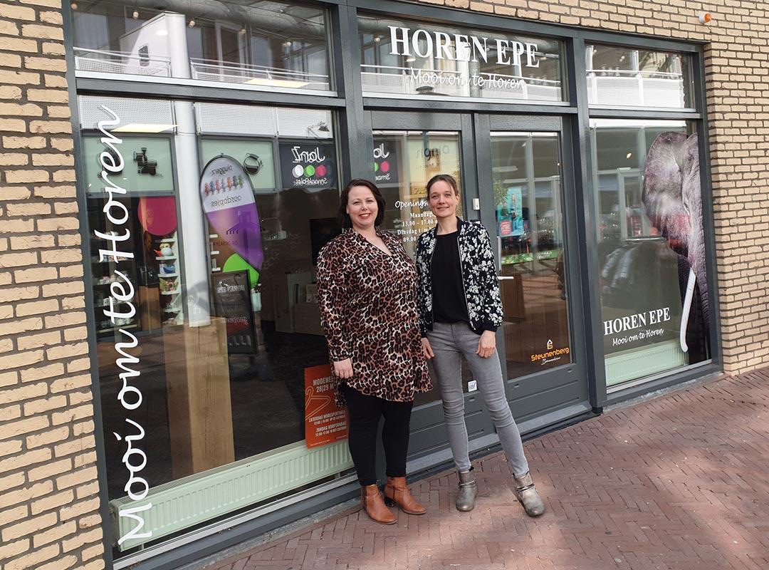 Renee en Esther voor de winkel van horen epe
